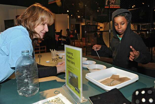 Education Program Manager Jenny Sumner teaches Uriah Gill, 7, of Schenectady about nanotechnology using hydrophobic sand and fabric at the miSci on Wednesday, Oct. 22, 2014 in Schenectady, N.Y. Kids experienced hands-on STEM: electricity demos, nanotechnology activities, planetarium show and interactive exhibits at miSci in partnership with Afterschool Works! (Lori Van Buren / Times Union) Photo: Lori Van Buren / 00029147A