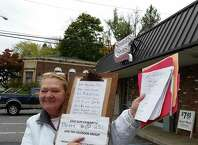 Castleton resident Annette Hammond holds up the more than 1,100 signatures she's collected to keep her local Stewart's Shop from closing. (Photo by Chris Churchill / Times Union)