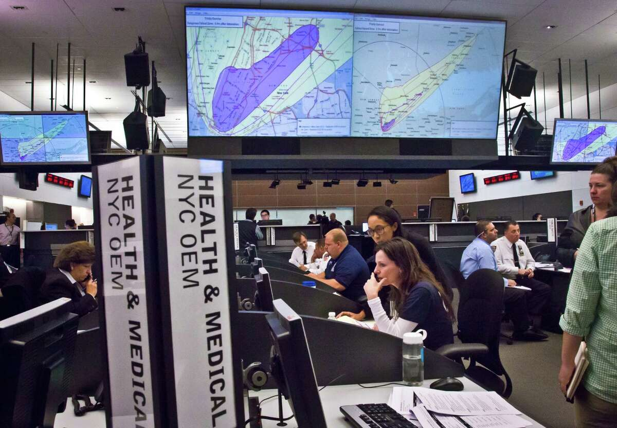 """A simulated doomsday map of a nuclear explosion in New York's Manhattan borough is projected overhead, as regional emergency and law enforcement officials participate in an """"Emergency Management Castastrophic Exercise Program"""" on Wednesday Oct. 22, 2014, at the Office of Emergency Management in New York. (AP Photo/Bebeto Matthews) ORG XMIT: NYBM101"""