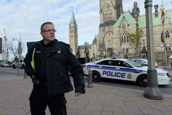 A police officer secures the scene of a shooting on Parliament Hill in Ottawa on Wednesday.  A soldier standing guard at the National War Memorial in Ottawa was shot and killed.