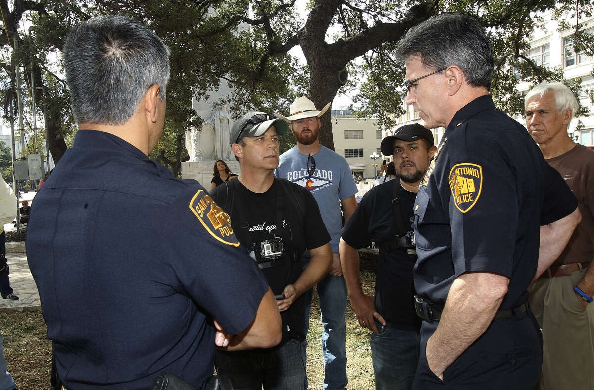 Mark Harrington, executive director of Ohio-based Created Equal (center), speaks with Police Chief William McManus about setting up equipment in Alamo Plaza that would display abortion images.