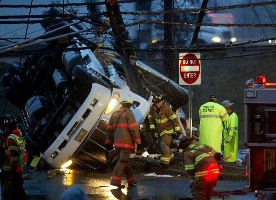 Shortly after 600 am, Milford firefighters and state police work on an overturned tractor trailer, Wednesday, Feb. 24, 2010, on the I95 northbound off ramp in Milford. Photo: Phil Noel / Connecticut Post