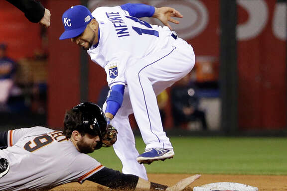 Royals second baseman Omar Infante gives the Giants' Brandon Belt a facial while catching Belt wandering off second base during the fourth inning Wednesday night.
