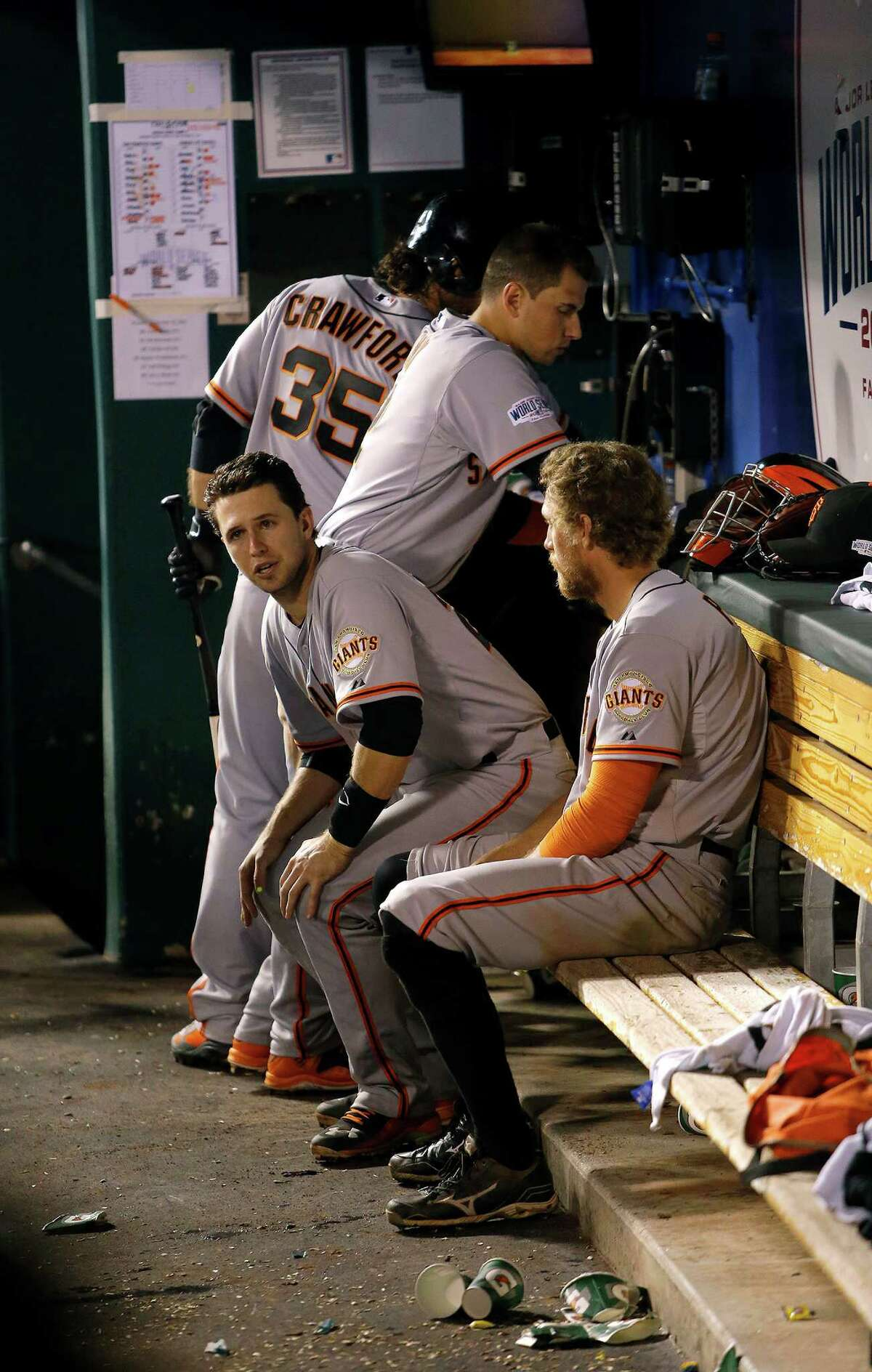 Giants Buster Posey and Hunter Pence sit in the dugout in the top of the ninth inning during Game 2 of the World Series at Kauffman Stadium on Wednesday, Oct. 22, 2014 in Kansas City, Mo.