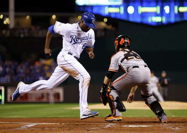 San Francisco Giants catcher Buster Posey waits for the throw as Kansas City Royals Lorenzo Cain scores on an RBI single by Billy Butler during the first inning of Game 2 of baseball's World Series Wednesday, Oct. 22, 2014, in Kansas City, Mo. (AP Photo/Matt Slocum)  ORG XMIT: WS337 Photo: Matt Slocum / AP