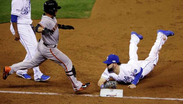 Kansas City Royals' Eric Hosmer (35) dives to first to beat San Francisco Giants' Gregor Blanco to the bag for an out during the third inning of Game 2 of baseball's World Series Wednesday, Oct. 22, 2014, in Kansas City, Mo. (AP Photo/Jeff Roberson)  ORG XMIT: WS143 Photo: Jeff Roberson / AP