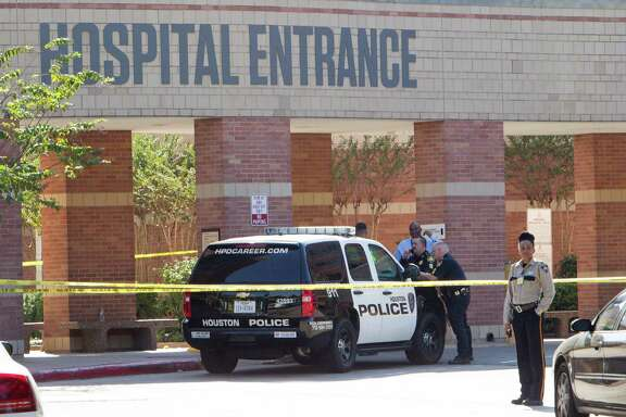 Law enforcement officers stand outside Ben Taub General Hospital following a shooting in the outpatient pharmacy on Wednesday, Oct. 22, 2014, in Houston. Two employees at the pharmacy at Ben Taub are dead after an apparent murder-suicide, officials said. Witnesses said a man shot a woman, then turned the gun on himself, said Houston Police Department spokesman John Cannon. They were pronounced dead a short time later.