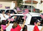 "Staff Sgt. Travis Palmer and his family are greeted with flag-waving supporters as they arrive to a ceremony to officially give them their hew home on Wednesday, Oct. 22, 2014, in Tomball. ""This is perfect,"" Sgt. Palmer said. ""I can't ask for another single thing. This is home."" The Palmers were given the keys to their newly-built, mortgage-free home, courtesy of H-E-B and Pulte Homes, in collaboration with local contractors and Operation Finally Home."