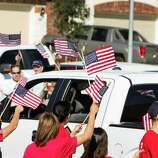 """Staff Sgt. Travis Palmer and his family are greeted with flag-waving supporters as they arrive to a ceremony to officially give them their hew home on Wednesday, Oct. 22, 2014, in Tomball. """"This is perfect,"""" Sgt. Palmer said. """"I can't ask for another single thing. This is home."""" The Palmers were given the keys to their newly-built, mortgage-free home, courtesy of H-E-B and Pulte Homes, in collaboration with local contractors and Operation Finally Home."""