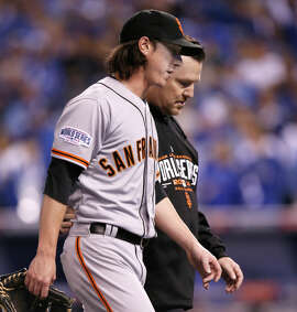 Tim Lincecum walks off the field with trainer Dave Groeschner after tweaking his back while pitching. He had retired five straight in the seventh and eighth innings.