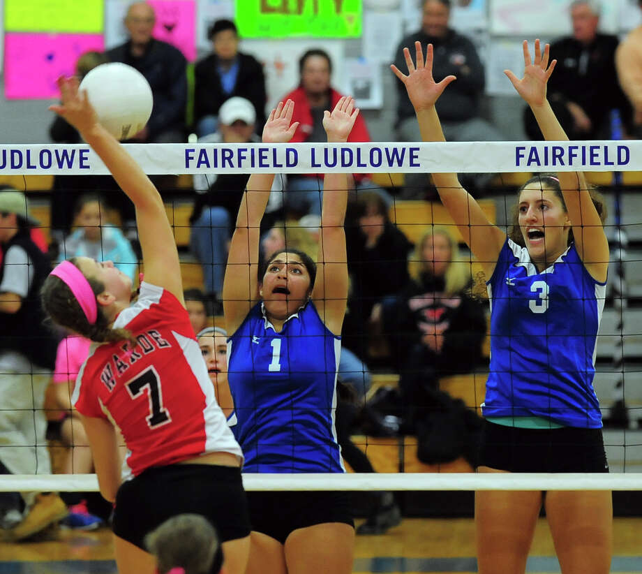 Warde's Jenny Schneider tries to score as Ludlowe's Andrea Alvarez (1) and Keki Cardenas (3) look to block during action in Wednesday's volleyball match in the Falcons gym. Ludlowe improved to 15-2 with a straight set victory. Photo: Christian Abraham / Connecticut Post