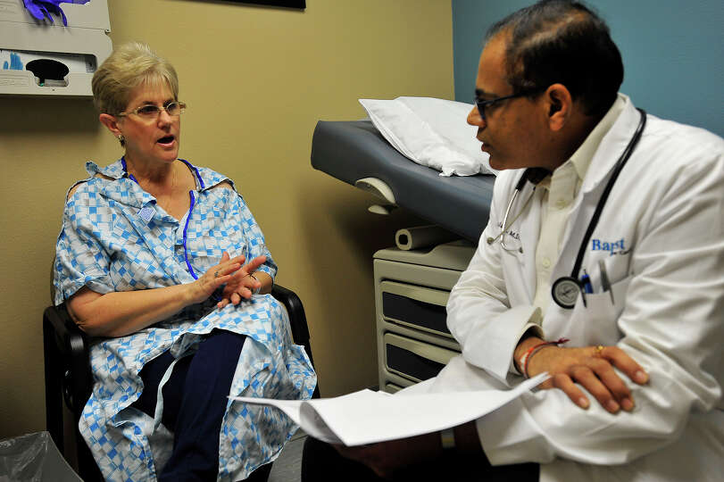 Jacquie Cross discusses medications with Dr. Ashok K. Malani during a follow-up appointment at the C