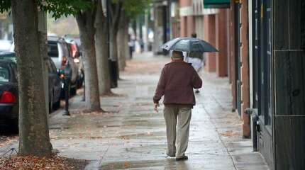 Joaquin Henriques, 63, of Danbury walks along Main Street in Danbury, Conn, on Saturday, October 4, 2014. Rain showers began in the morning, tapering off into the late afternoon with an accumulation of almost an inch of rain.