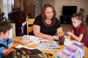 Lisa Peacock helps her grandchildren Marcus, 6, and Hayden, 7, with homework Monday October 20, 2014 in their home.