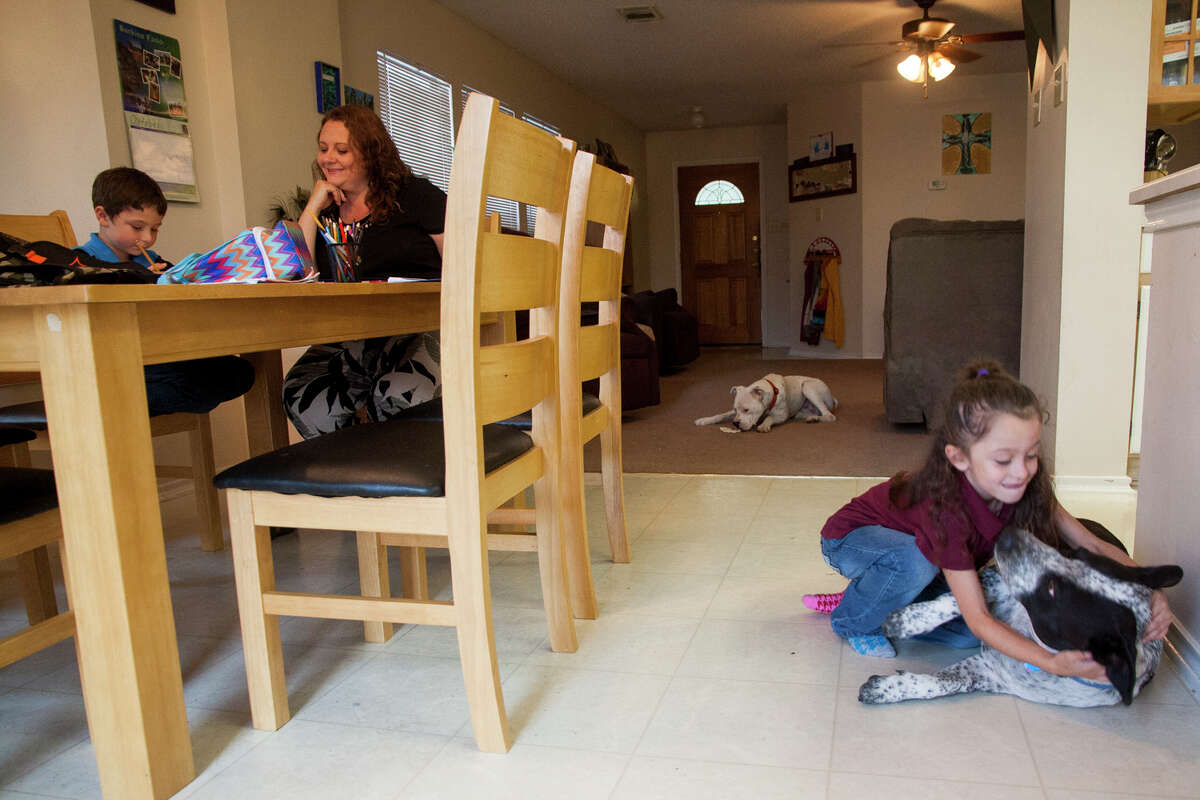 Lisa Peacock helps her grandchild Marcus, 6, with homework while Hayden, 7, plays with their dog Monday October 20, 2014 in their home.