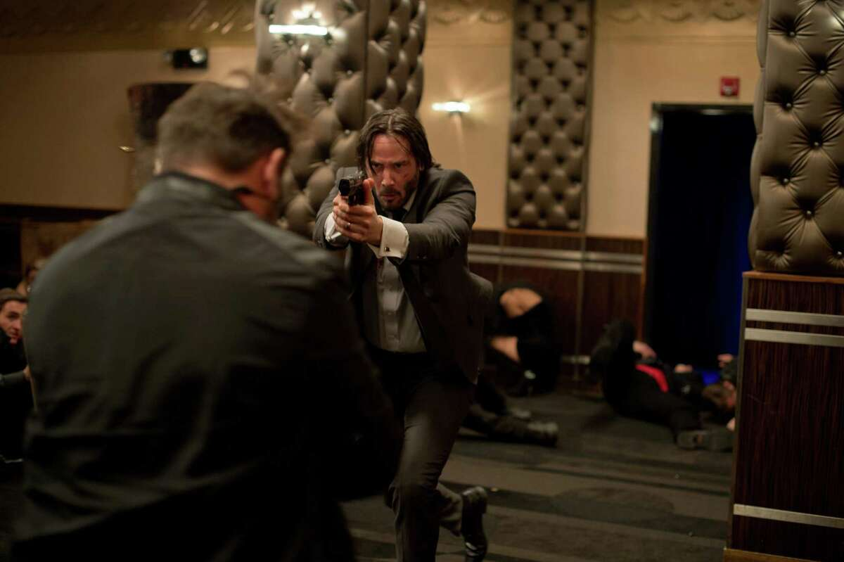 """This photo released by Lionsgate shows Keanu Reeves, center, as John Wick in a scene from the film, """"John Wick."""" (AP Photo/Lionsgate, David Lee)"""