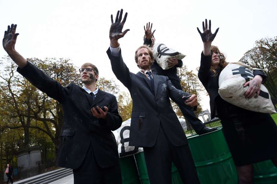 Oxfam activists dressed as corporate lobbyists of fossil fuel companies stage a demonstration ahead of an EU summit in Brussels on October 23, 2014. The activists are demanding that EU leaders resist pressure by the fossil fuel industry and agree to an EU 2030 climate and energy package that puts Europe on track to a clean energy future. European Union leaders are meeting at a summit in Brussels aimed at clinching a high-stakes deal on combating climate change and boosting efforts to fight the deadly Ebola virus. AFP PHOTO/EMMANUEL DUNANDEMMANUEL DUNAND/AFP/Getty Images Photo: EMMANUEL DUNAND, AFP/Getty Images