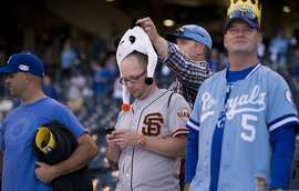 Kansas City Royals fan Todd Leach removes the panda hat from the head of his friend Larry Hovorka at Game 1 of baseball's World Series between the Royals and the San Francisco Giants at Kauffman Stadium in Kansas City, Mo., on Tuesday, Oct. 21, 2014. (AP Photo/The Sacramento Bee, Paul Kitagaki Jr.)