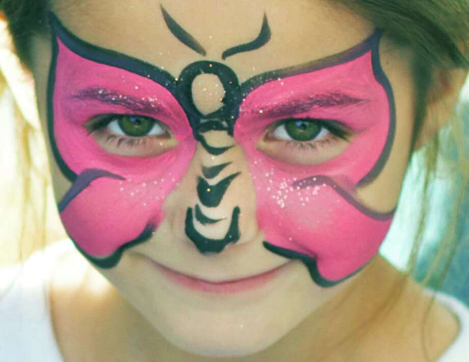 Kristin Rogg, 7, of  New Milford has a beautiful butterfly painted on her face at the Village Center for the Arts booth during the sixth annual New Milford Harvest Festival, hosted Oct. 12, 2014 in the New Milford village center by the Greater New Milford Chamber of Commerce. Photo: Trish Haldin / The News-Times Freelance