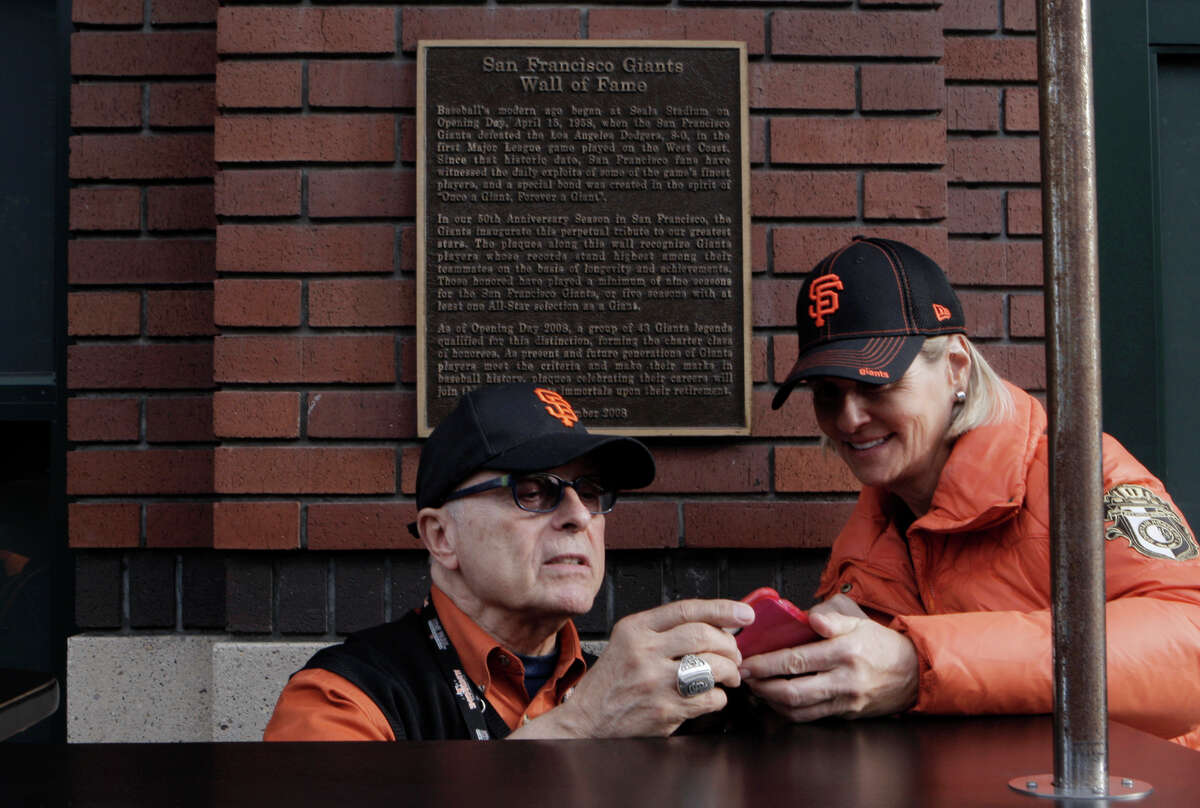 Martin Dias, working the Muni kiosk in front of AT&T Park, tells Karen Lines of Menlo Park where her seats are.