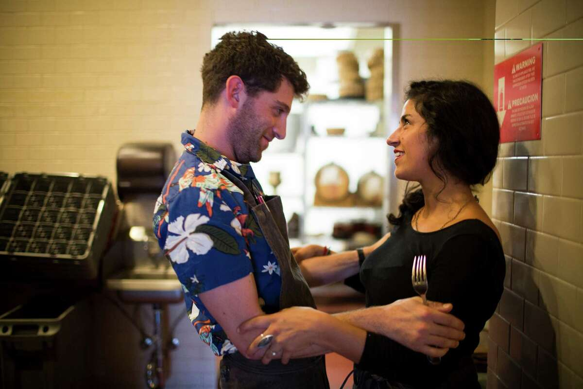 Line cook Danny Keiser shares a moment with server Rose DeStefano before opening at Camino in Oakland on Oct. 22, 2014. Camino will soon get rid of its tip system in favor of a service charge system. DeStefano said she thinks it will help keep her pay more steady, especially on slow nights.