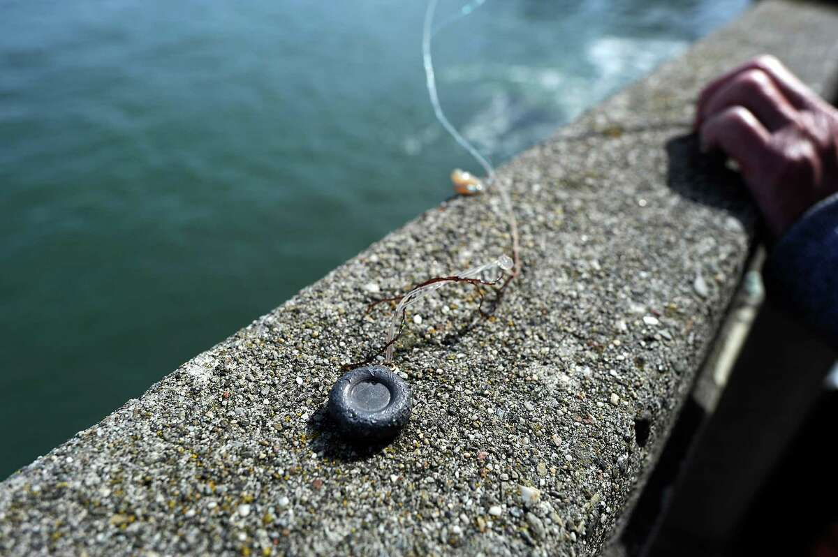 A lead weight is seen attached to a man's fishing line as he fishes off the pier at Aquatic Park in San Francisco on Oct. 22, 2014.