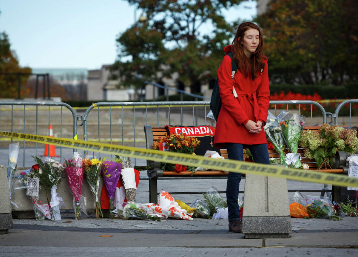 A woman mourns at a makeshift memorial near the National War Memorial where a corporal was shot dead a day earlier, in Ottawa.