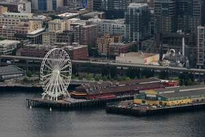 Seattle's Great Wheel stands out on the pier in downtown as seen from the Oracle chase plane on Thursday, August 2, 2012. Tucker, internatonally recognized as one of the premier civilian aerobatic performers worldwide, has logged over 24,000 flight hours and has been performing since the 1970s. (Photo by Lindsey Wasson)