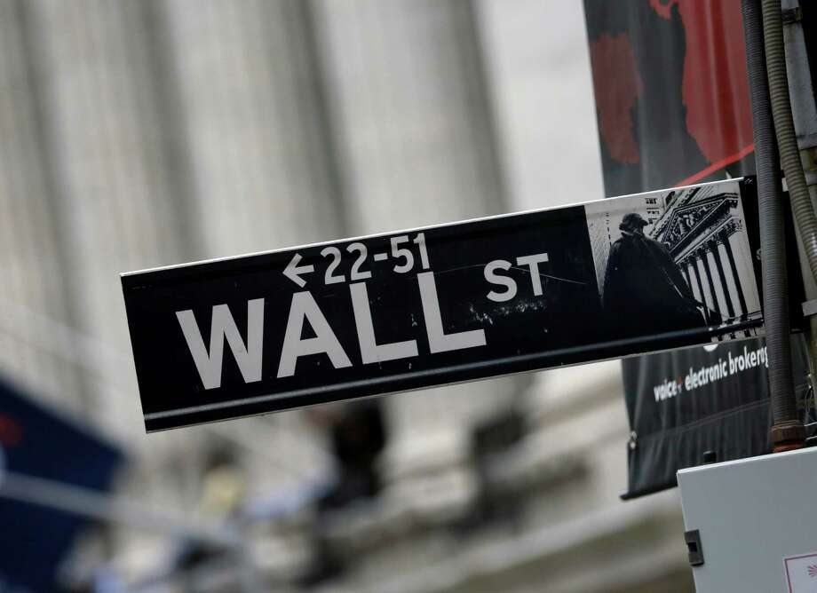 This Oct. 2, 2014 photo shows a Wall Street sign adjacent to the New York Stock Exchange, in New York. Earnings gains from General Motors, 3M and other big companies are driving stocks sharply higher in early trading Thursday, Oct. 23, 2014. (AP Photo/Richard Drew) ORG XMIT: NYBZ101 Photo: Richard Drew / AP