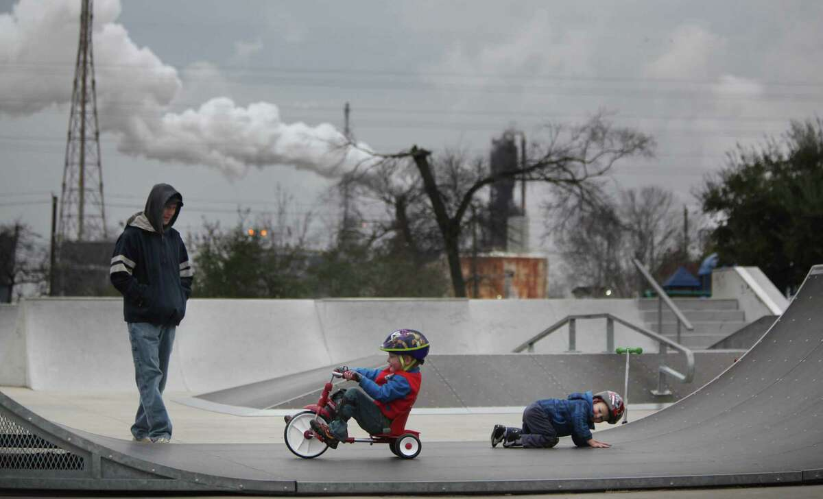 Aaron Smith, of Baytown, looks at his sons Vaughn Smith, 4, and Vance Smith, 2, play in the skate park area at Unidad Park across the street from the Exxon Mobil Baytown Complex on Friday, Feb. 7, 2014, in Baytown. ( Mayra Beltran / Houston Chronicle )