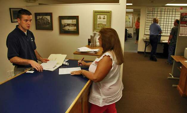 Times Union staff photo by John Carl D'Annibale       Halfmoon resident Dave Roberts, left, recieves info on a building permit from town Building Dept. employee Denise Mikol in her department's newly renovated offices Thursday June 1, 2006. Photo: John Carl D'Annibale / Albany Times Union