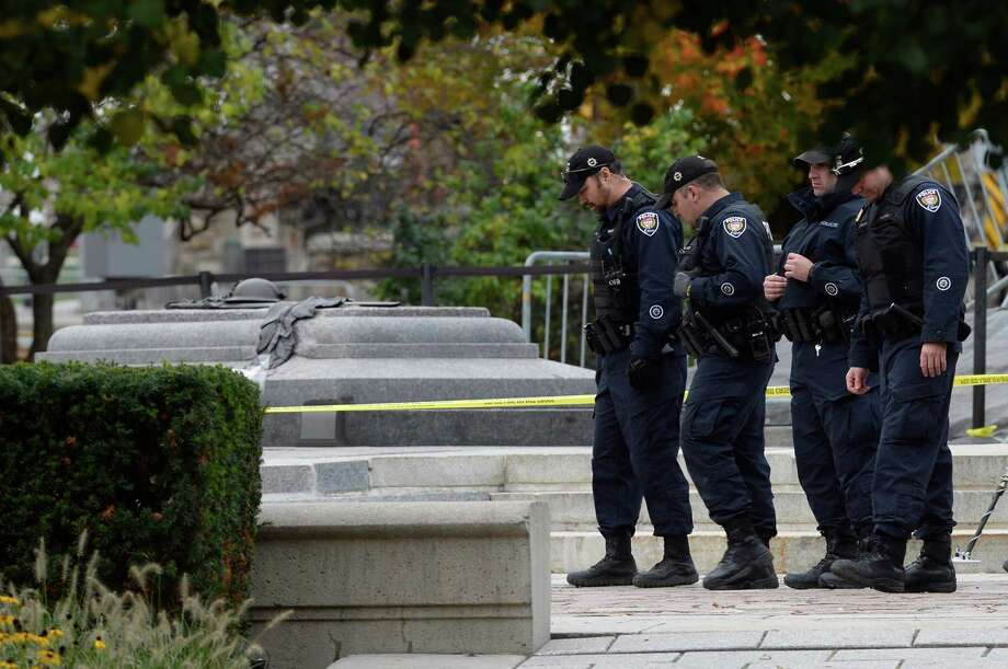 Police officers look for evidence at the National War Memorial in Ottawa on Thursday, Oct. 23, 2014. Cpl. Nathan Cirillo was killed Wednesday at the National War Memorial by a gunman who then raced to Parliament Hill, where he was killed in a gunfight in the halls of the Centre Block.  (AP Photo/The Canadian Press, Adrian Wyld)  ORG XMIT: AJW718 Photo: Adrian Wyld / The Canadian Press
