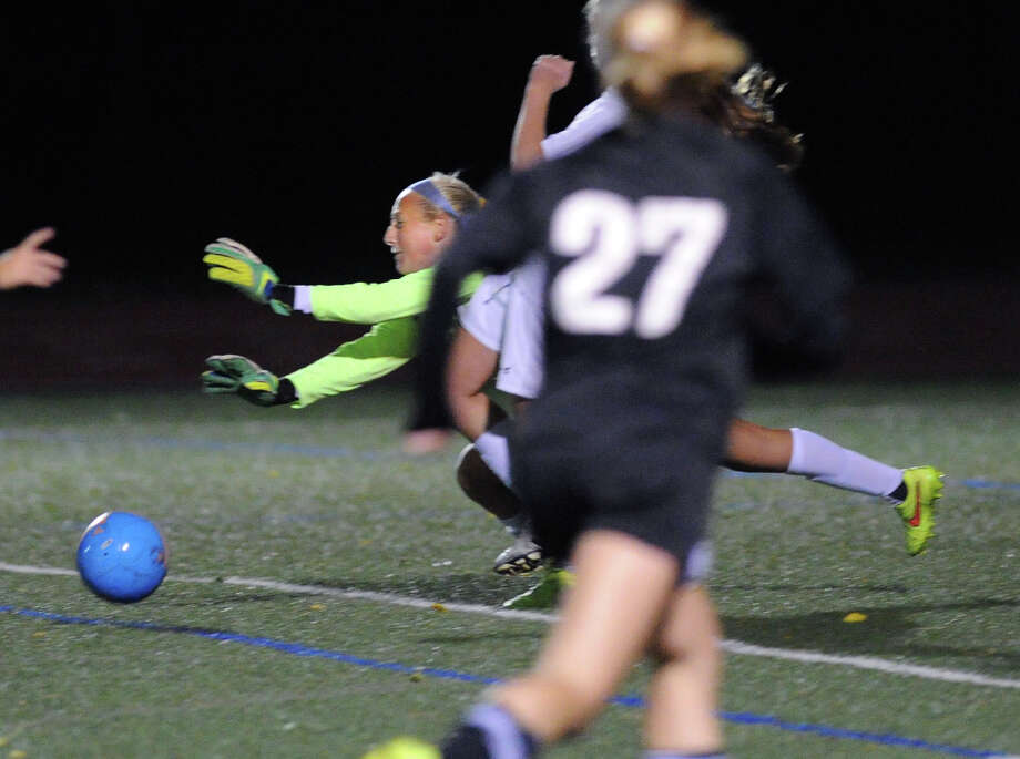 Greenwich goal keeper Emma Barefoot, center, makes a diving stop in the final minutes of the girls high school soccer match between Greenwich High School and Trumbull High School at Greenwich, Conn., Thursday, Oct. 23, 2014. Looking on is Trumbull's Amelia Crosley (#27). Greenwich won the match, 1-0. Photo: Bob Luckey / Greenwich Time