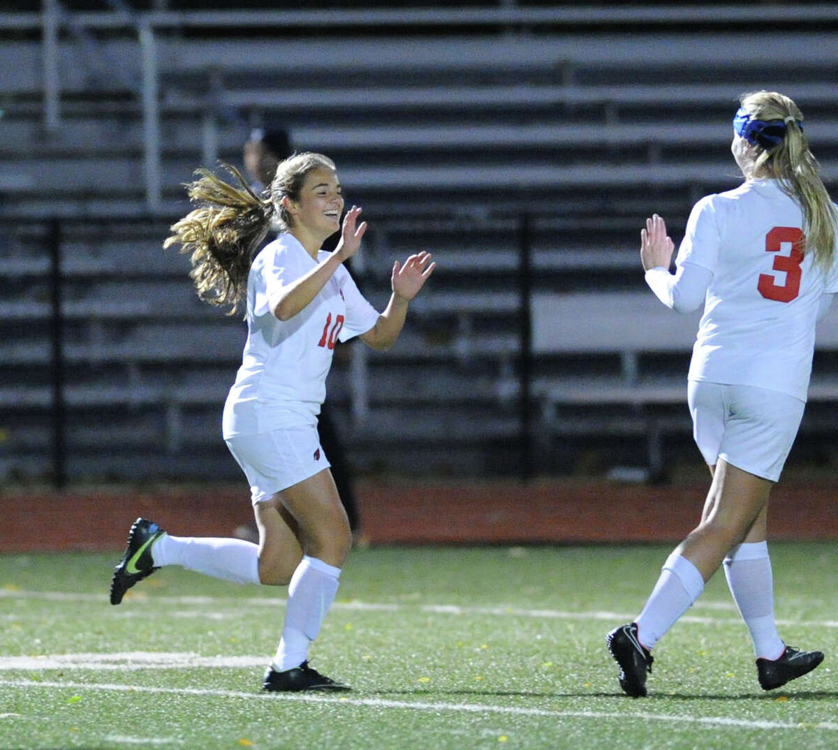 At left, Emily Berzolla (#10) of Greenwich smiles after scoring the only goal of the match during first half action of the girls high school soccer match between Greenwich High School and Trumbull High School at Greenwich, Conn., Thursday, Oct. 23, 2014. At right is Berzolla's Greenwich teammate Treloara Harrisson (#3). Greenwich won the match, 1-0.