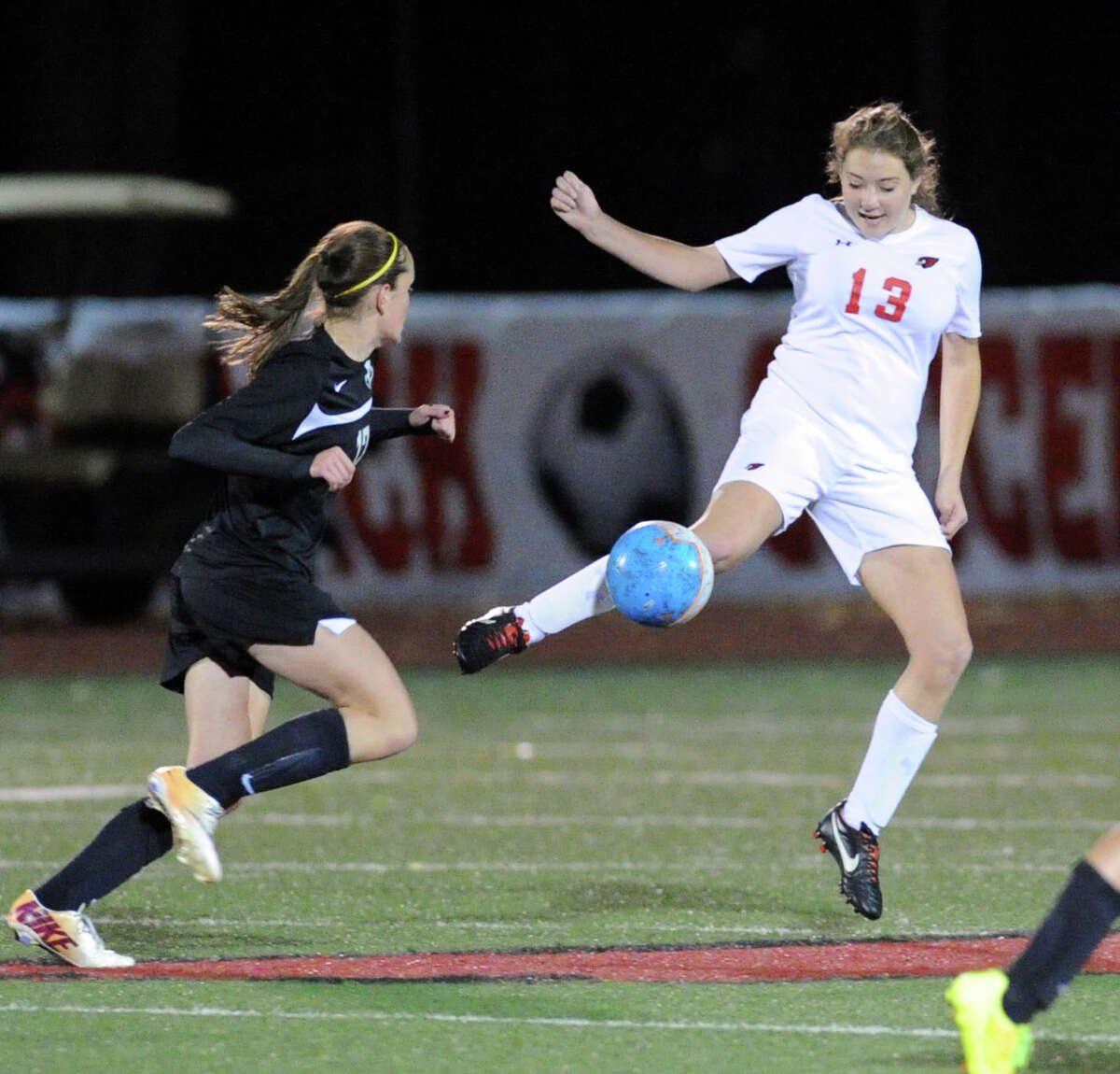 At right, Lindsay Alfano (#13) of Greenwich passes during the girls high school soccer match between Greenwich High School and Trumbull High School at Greenwich, Conn., Thursday, Oct. 23, 2014. Greenwich won the match, 1-0.
