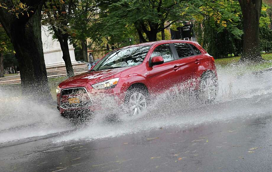 An SUV makes a big splash while driving through a puddle in Washington Park Thursday, Oct. 23, 2014, in Albany, N.Y.  (Lori Van Buren / Times Union) Photo: Lori Van Buren