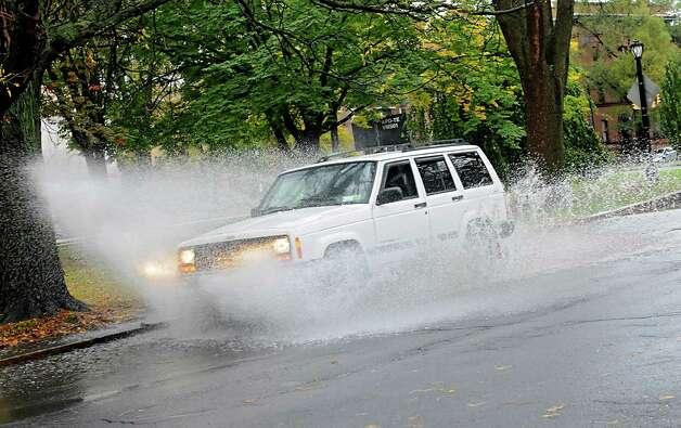 An SUV makes a big splash while driving through a puddle in Washington Park Thursday, Oct. 23, 2014, in Albany, N.Y.  (Lori Van Buren / Times Union) Photo: Lori Van Buren