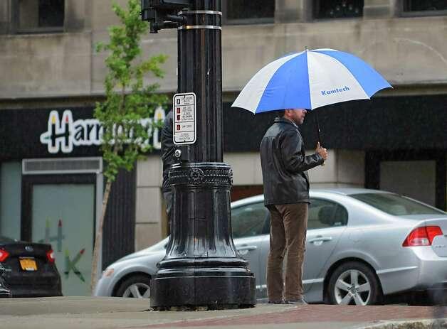 A pedestrian waits to cross South Pearl St. along State St. on a rainy day Thursday, Oct. 23, 2014 in Albany, N.Y.  (Lori Van Buren / Times Union) Photo: Lori Van Buren