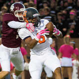 Seven Lakes wide receiver Alick Arnold (6) catches a touchdown pass as Cinco Ranch cornerback Jacob Smith (7) defends during the first half of a high school football game at  Rhodes Stadium, Thursday, Oct. 23, 2014, in Houston.
