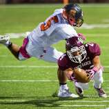 Cinco Ranch wide receiver Corey Ceniceros (C) (24) dives for a first down past Seven Lakes defensive back Junior Henderson (5) during the first half of a high school football game at  Rhodes Stadium, Thursday, Oct. 23, 2014, in Houston.