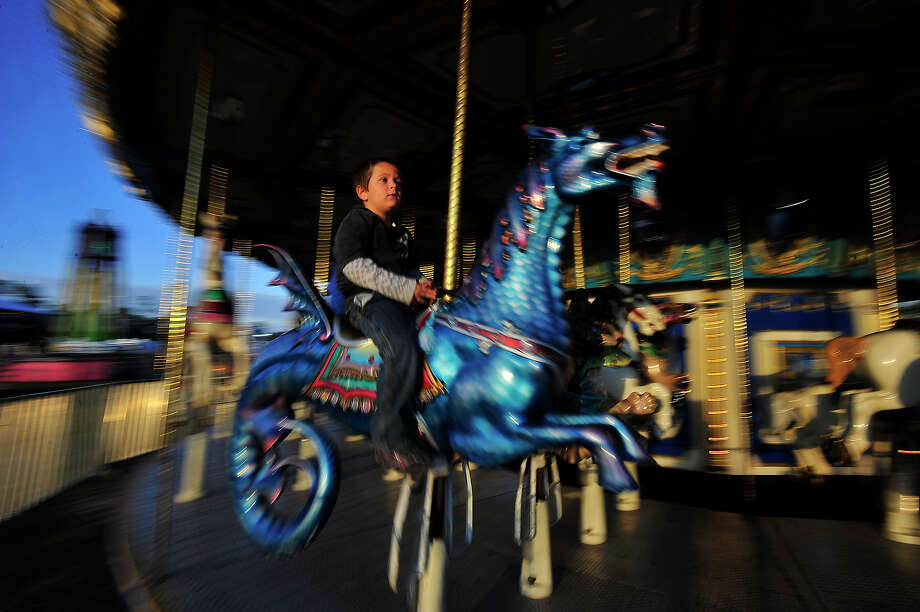 Six-year-old Blake Phillips takes in the activity on the park grounds as he goes for a ride on the carousel on the opening night of the Village Creek Festival in Lumberton Thursday. The event runs throughout the weekend at Lumberton City Park and features carnival rides and games, entertainment, food vendors, and various contests. Photo taken Thursday, October 23, 2014 Kim Brent/@kimbpix Photo: Kim Brent / Beaumont Enterprise