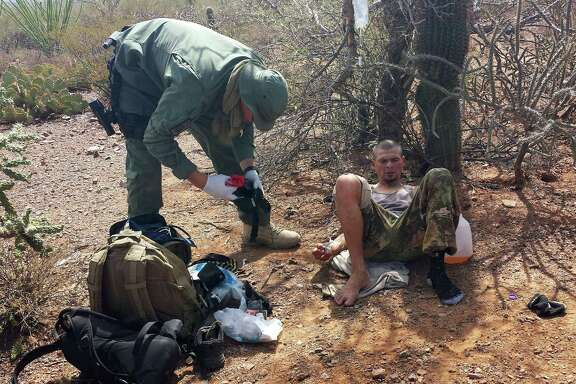 A U.S. Border Patrol agent near the border in Sells, Ariz., helps a man suspected of being a drug mule by setting up an IV for dehydration.