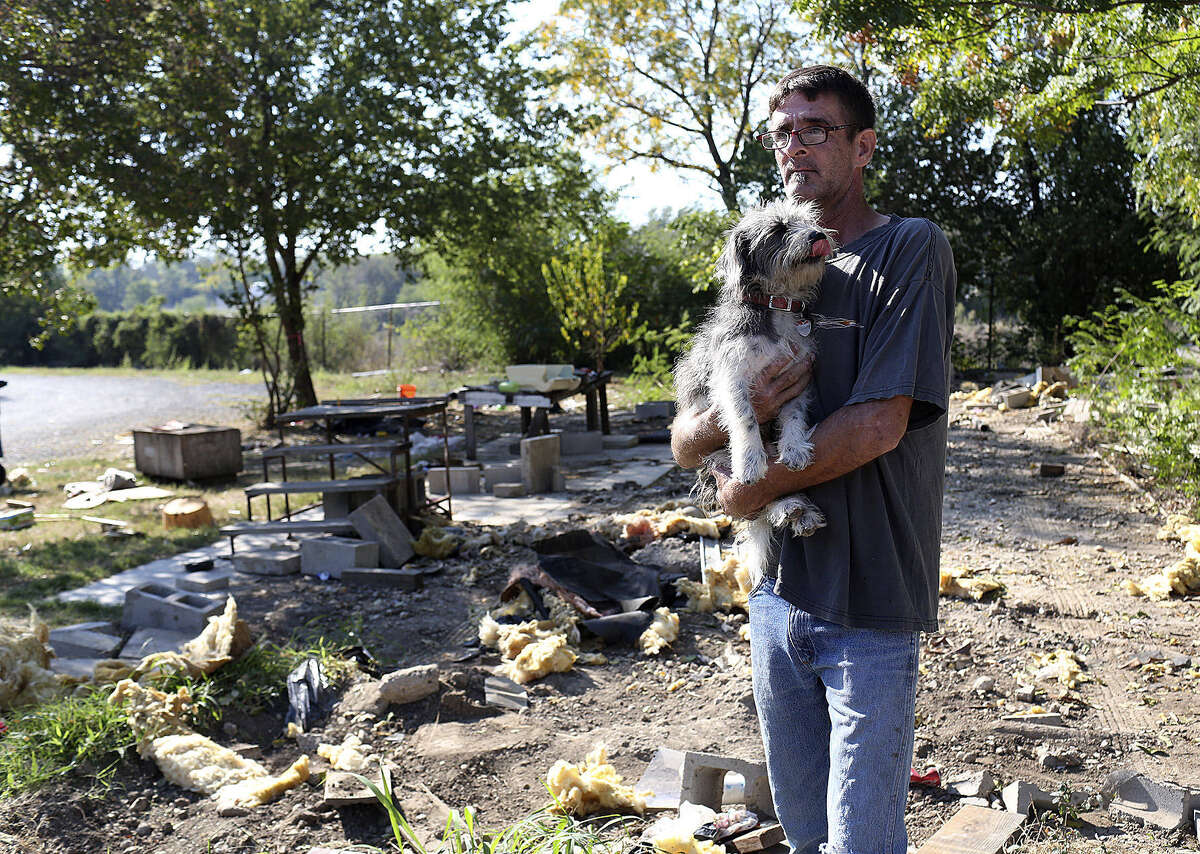 Jeffrey Alan Draper holds his dog Dust Mop after the mobile home he shares with his mother, Carol Thompson, is driven away from Mission Trails.