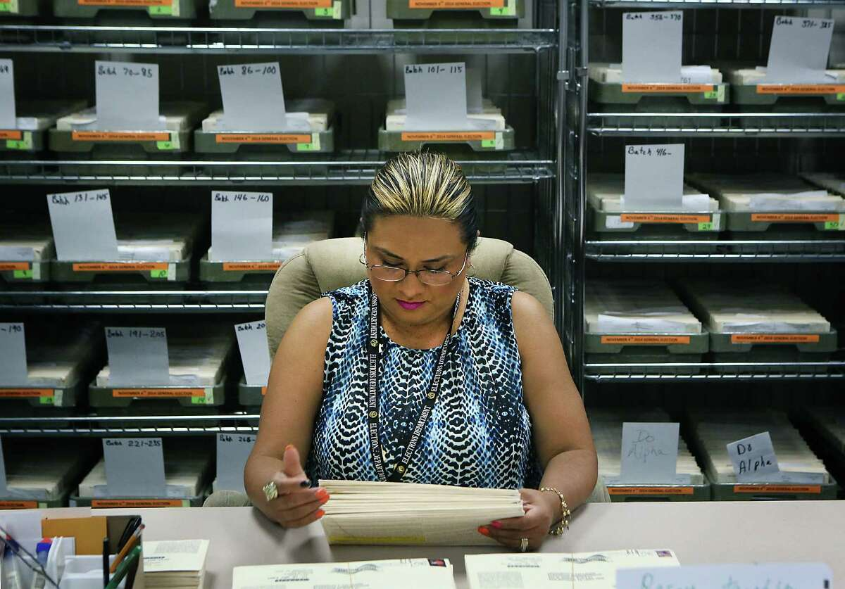 Bexar elections worker Maria Escobar goes through mailed-in ballots, making sure they're signed.