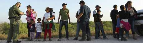 U.S. Border Patrol agents question a group of adult and minor migrants who walked up to them southwest of McAllen.