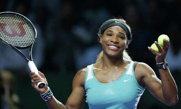 Serena Williams of the US reacts after hitting an autographed ball into the crowd following her win over Canada's Eugenie Bouchard during their singles match at the WTA tennis finals in Singapore,Thursday, Oct. 23, 2014. (AP Photo/Mark Baker) ORG XMIT: XMB130 Photo: Mark Baker / AP