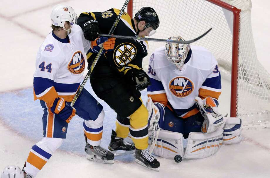 New York Islanders goalie Chad Johnson, right, makes a save as Islanders defenseman Calvin de Haan (44) tries to clear Boston Bruins' Reilly Smith away from the crease during the third period of an NHL hockey game in Boston, Thursday, Oct. 23, 2014.  The Islanders defeated the Bruins 3-2. (AP Photo/Charles Krupa) ORG XMIT: MACK110 Photo: Charles Krupa / AP