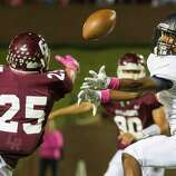 Cinco Ranch defensive back Taylor Jiral (25) breaks up a pass intended for Seven Lakes wide receiver  Bryan Moore (2) during the second half of a high school football game at  Rhodes Stadium, Thursday, Oct. 23, 2014, in Houston.