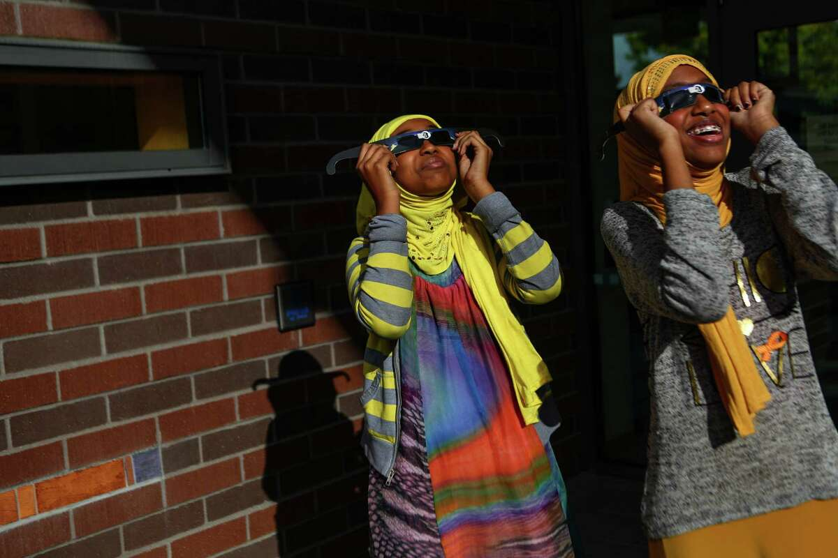 Young guests use protective eyewear during a solar eclipse viewing party at the High Point Branch of the Seattle Public Library. Photographed on Thursday, October 23, 2014.