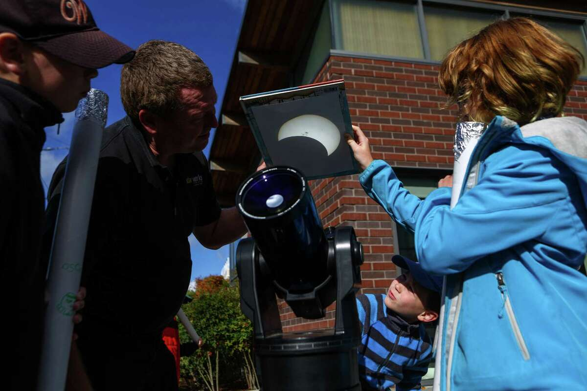 Andrew McCarty and his daughter Zoe McCarty, 11, right, look at a projected image of the sun during a solar eclipse viewing party at the High Point Branch of the Seattle Public Library. Photographed on Thursday, October 23, 2014.